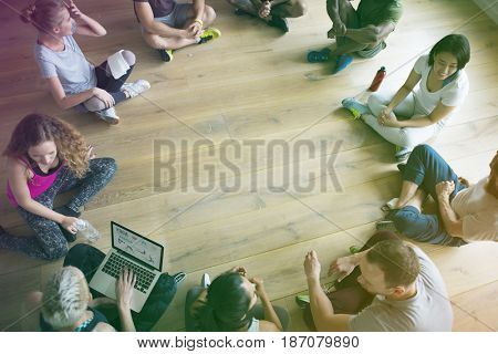 People seated in a circle in yoga class