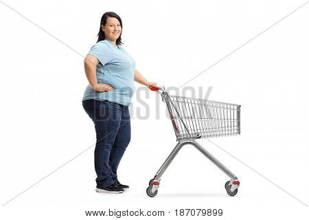 Full length portrait of an overweight woman with an empty shopping cart waiting in line isolated on white background
