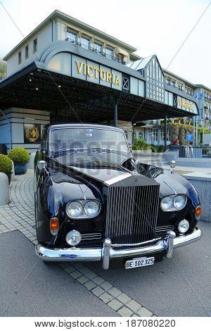 INTERLAKEN, SWITZERLAND - MAY 5, 2017: Rolls-Royce luxury car in front of historic Victoria Jungfrau Grand Hotel and Spa in Interlaken, Switzerland.