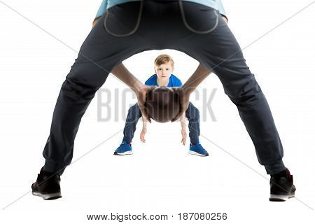 partial view of father and son playing rugby together isolated on white