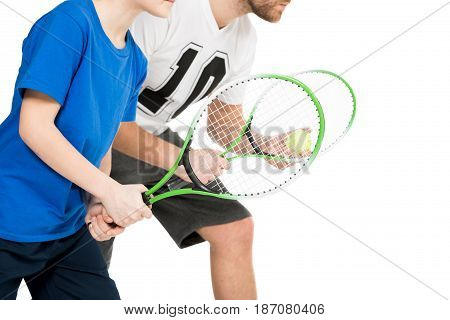 Partial View Of Father And Son With Tennis Racquets Isolated On White