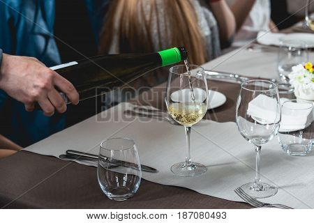 a lot of different wine glasses on the table at wine tasting. sommelier at wine tasting talks about how different wines suited to different dishes