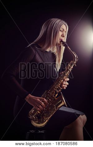 Female jazz musician sitting on a chair and playing a saxophone during a concert