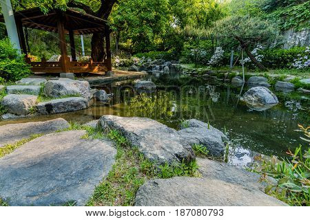 Landscape of a wooden gazebo next to a small pond with a small waterfall in a public park in South Korea