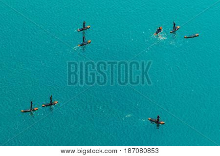 Aerial view of unrecognizable group of people stand up paddle boarding on water surface for sport fun leisure or recreational pursuit. Enjoying summer SUP activity for holiday vacation.