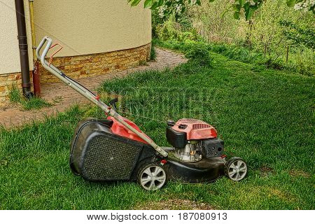 Lawn mower on the lawn near the wall of the building