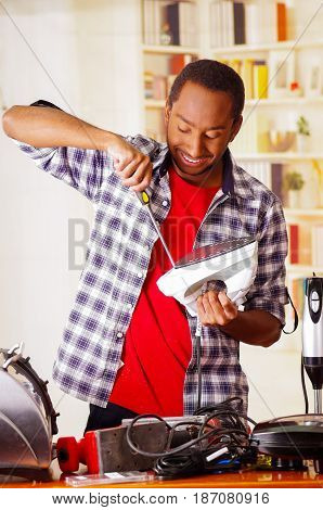 Happy Young African Ecuadorian male Technician repairing an iron with a screwdriver.
