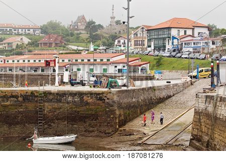 SPAIN CANTABRIA COMILLAS - JULY 7 2016: Port and marine during an outflow. A view of the city from port in foggy summer day after a rain