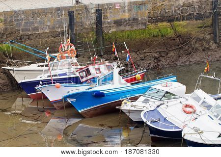 Motor boats of the boat in a marine during an outflow. Low water level has bared seaweed on a stone wall. Boats lie on one side