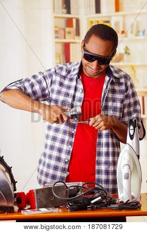 Happy Young African Ecuadorian male Technician wearing protection glasses and using a metal cutter with office background.