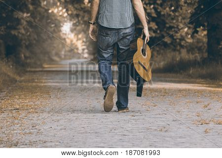 Free travel with guitar. With music instrument on the trip. Person is walking with guitar on the path.