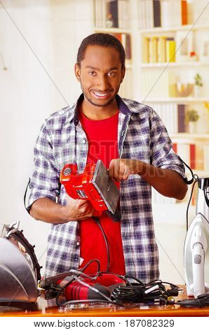 Happy Young African Ecuadorian male Technician fixing a red sander with his screwdriver on office background.