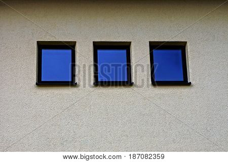 Three square small windows on the gray wall of the building