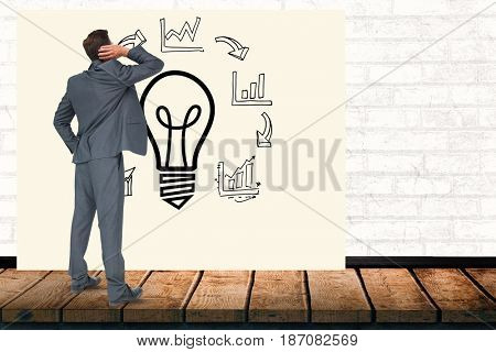 Digital composite of Confused businessman looking at light bulb amidst various graphs on billboard in office