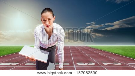 Digital composite of Digital composite image of businesswoman with laptop at starting point on racing track