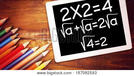 Digital composite of High angle view of various mathematical formula by color pencils on wooden table