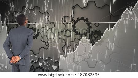 Digital composite of Digital composite image of businessman looking at graphs and gears on grid