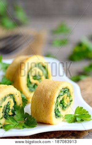 Cheese and herbs omelette rolls garnished with fresh parsley. Easy stuffed omelette rolls with grated cheese and finely chopped herbs. Children friendly breakfast idea. Rustic style. Vertical photo