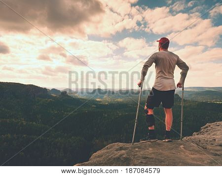 Happy Man With Broken Leg In Immobilizer And Medicine Pole Stay Finnaly On  Peak.