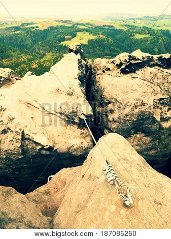 Iron Twisted Rope Stretched Between Rocks In Climbers Patch Via Ferrata.  Rope Fixed In Rock