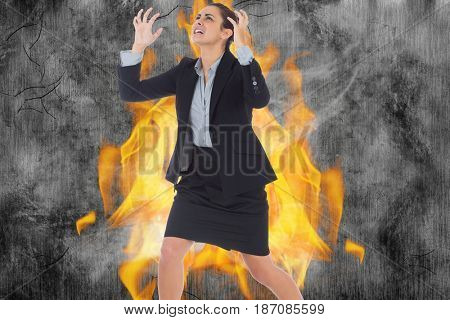 Digital composite of Angry businesswoman gesturing against fire