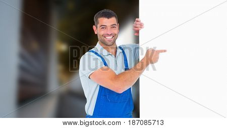 Digital composite of Portrait of smiling manual worker pointing at blank billboard