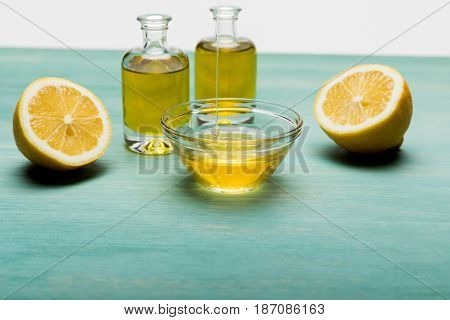 Close-up View Of Essential Oil In Small Bottles, Honey In Bowl And Sliced Lemon On Wooden Table