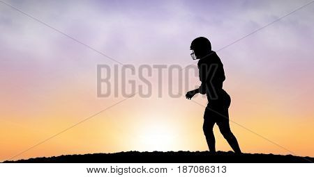 Digital composite of Silhouette sportsperson walking on field against sky during sunset