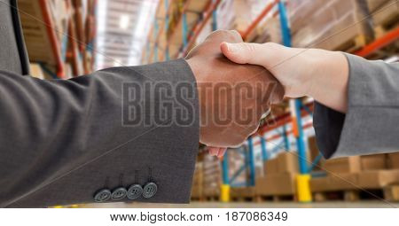Digital composite of Male and female business partners shaking hands in warehouse