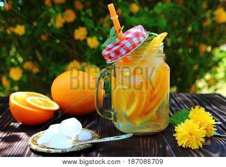 orange lemonade with ice cubes and flowers