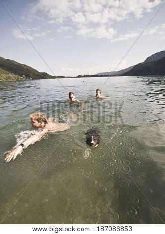 Caucasian friends swimming in lake with dog