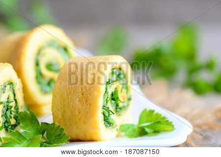Cheese and herbs omelet rolls garnished with parsley. Simple stuffed omelet rolls with grated cheese and finely chopped herbs. Kid friendly breakfast idea. Rustic style. Closeup