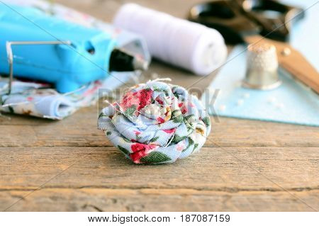 Floral textile brooch. Boho flower brooch decorated with beads, hot glue gun, scissors, thread spool, thimble, felt sheet on old wooden table. Summer women brooch crafts idea. Craft background