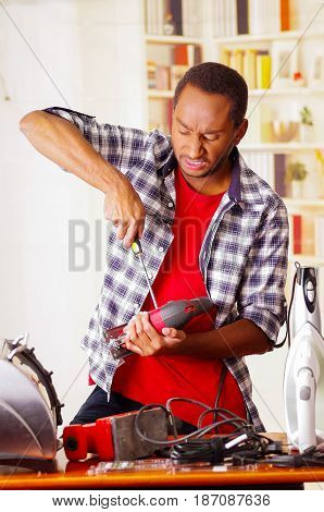 Young African Ecuadorian male Technician pucker his face while he is fixing a wood sander with a screwdriver.