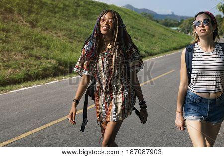 Group of Diverse Backpacker Women Walking along The Street Side