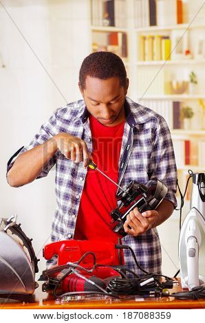 Young African Ecuadorian male Technician repairing a toaster with a screwdriver.