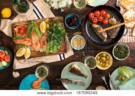 Dinner table with shrimp fish grilled salad different snacks and white wine top view