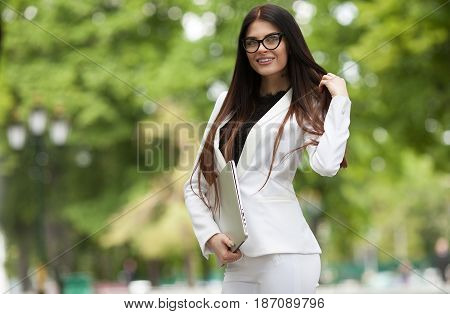 Business Mobility Concept With A Portrait Of A Young Business Woman In White Suit On The Move Around Town With A Laptop In Hand
