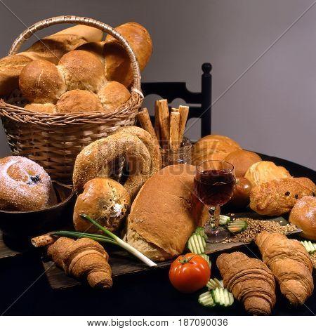 Assortment of bread croissants bagels tomato cucumbers onion wine basket