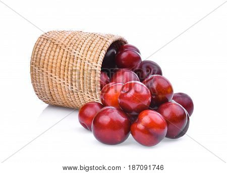 cherry plum in wooden basket isolated on white background