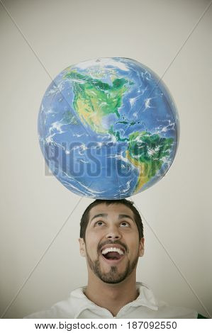 Smiling man balancing globe in his head
