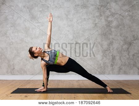 Young Woman Practicing Yoga Pose Bikram Triangle, Trikonasana Against Texturized Wall / Urban Backgr