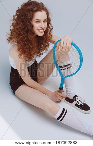 Smiling Hipster Girl Sitting And Holding Tennis Racket And Ball