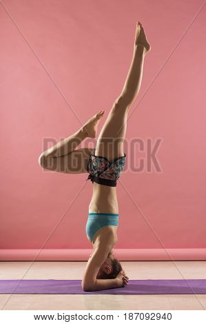 Sporty Beautiful Young Female Doing Yoga Supported Headstand /.salamba Sirsasana On Pink Background