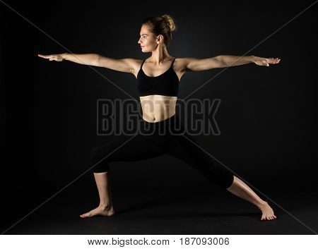 Sporty Beautiful Young Female Doing Yoga Warrior Pose Left / Virabhadrasana  On Dark Black Backgroun