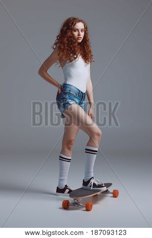 Attractive Young Hipster Woman Standing On Skateboard And Posing Isolated On Grey