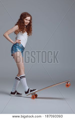Smiling Young Hipster Woman Standing On Skateboard Isolated On Grey