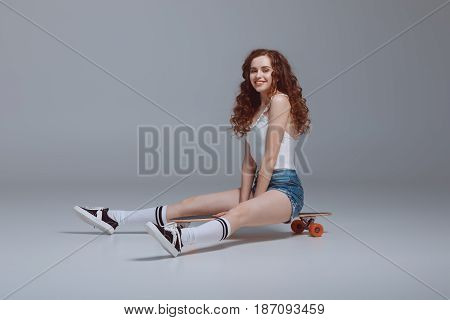 Smiling Young Hipster Woman Sitting On Skateboard Isolated On Grey