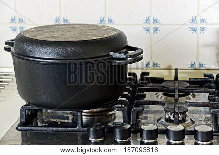 Black cast-iron pot on the gas stove