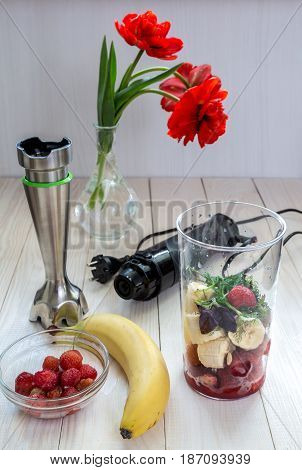 Mixer and fruit for smoothies on a wooden table.